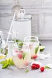 Cocktail froid d'été avec les chaux et la framboise Photo stock