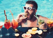 Cocktail with fruit at bearded man in pool. Man swimming and drink alcohol. Summer vacation at Miami or Maldives. Pool. Party, vitamin and dieting. Relax at sea stock images