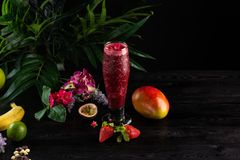 Cocktail with fruits and berries in a tall glass on a dark background stock photography