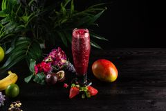 Cocktail with fruits and berries in a tall glass on a dark background royalty free stock photos