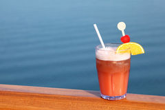 Cocktail with fruits in glass on ship deck rail Stock Images