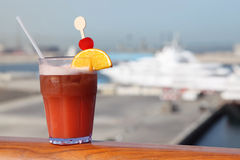 Cocktail with fruits in glass on ship deck rail Royalty Free Stock Photography