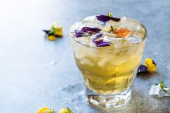 Cocktail glacé de fines herbes de thé avec les fleurs comestibles et la glace écrasée photos libres de droits