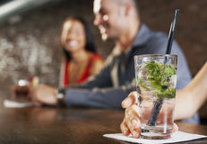 Cocktail Glass With Blurred Couple Behind Royalty Free Stock Photo