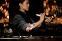 Cocktail glass on the blurred foreground of bartender girl holding a steel shaker. On the bar counter royalty free stock photography