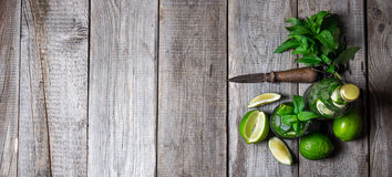 Cocktail in glass and bottle , also mint and limes on a wooden table . Free space for text. Royalty Free Stock Image