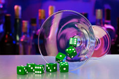 Cocktail glass with dices in casino bar Stock Photos