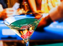 Cocktail glass in front of gambling table Royalty Free Stock Photography