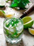 Cocktail in a glass with ice cubes, lime, mint leaves and rum . Stock Photo
