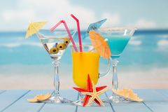 Cocktail, glass of juice and alcohol with olives, umbrellas and. Cocktail, a glass of juice and alcohol with olives, umbrellas and straws, starfish on the stock photos