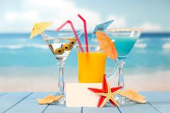 Cocktail, glass of juice and alcohol with olives, umbrellas, straws, blank card and starfish, against background of sea. Cocktail, a glass of juice and alcohol stock photo