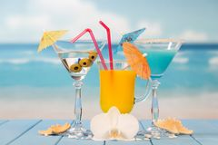 Cocktail, glass of juice and alcohol with olives, umbrellas and. Cocktail, a glass of juice and alcohol with olives, umbrellas and straws, starfish, seashells royalty free stock images