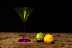 Cocktail glass and lemon and lime on wooden surface Stock Photography