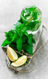 Cocktail glass - mint, ice, rum and lime on stone pedestal . Stock Photo