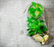 Cocktail glass - mint, ice, rum and lime on a stone pedestal . Stock Photos