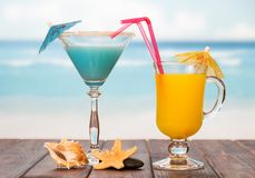 Cocktail and glass of orange juice with umbrellas, straws, starfish, smooth stone and sea shell on background of sea. Cocktail and a glass of orange juice with royalty free stock photo