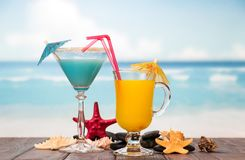 Cocktail and glass of orange juice with umbrellas, straws, starf Stock Photos