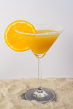 Cocktail Glass. Orange cocktail with orange slice on edge. On the ground is beach Sand Royalty Free Stock Photos