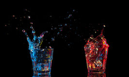 Cocktail in glass with splashes on dark background. Party club entertainment. Mixed light. stock photography