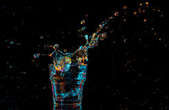 Cocktail in glass with splashes on dark background. Party club entertainment. Mixed light. Royalty Free Stock Photos