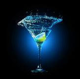 Cocktail in glass with splashes. And lemon on dark background. Party club entertainment. Mixed light Royalty Free Stock Image