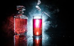 Cocktail glass splashing on dark toned smoky background or colorful cocktail in glass. Party club entertainment. Mixed light royalty free stock photo