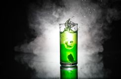 Cocktail glass splashing on dark toned smoky background or colorful cocktail in glass. Party club entertainment. Mixed light royalty free stock photography