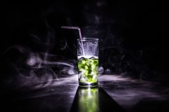 Cocktail glass splashing on dark toned smoky background or colorful cocktail in glass. Party club entertainment. Mixed light. Selective focus stock images