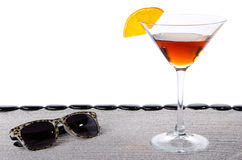 Cocktail glass with sunglasses and  black pebbles Stock Images