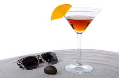 Cocktail glass with sunglasses and a pebble on the sand Stock Photography
