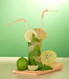 Cocktail glass, umbrellas, juicy lime and napkin Royalty Free Stock Photo