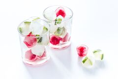Cocktail glasses with berries in ice cubes on white table