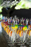 Cocktail glasses with colorful accessories: cocktail rolls, cocktail umbrellas and orange slices. And sequins stock photos