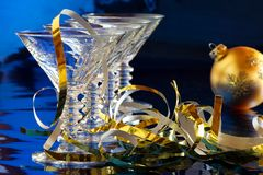 Cocktail glasses with golden Christmas decoration. Row of cocktail glasses with golden Christmas decoration against blue background Royalty Free Stock Photography