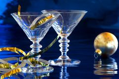 Cocktail glasses with golden Christmas decoration. Two cocktail glasses with golden serpentine and Christmas ball with reflection against blue background Stock Photography
