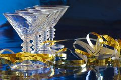 Cocktail glasses with golden serpentine. A row of four cocktail glasses with golden serpentine against blue background with reflection Royalty Free Stock Image