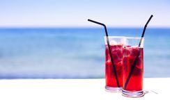 Cocktail glasses on sea background. Two cocktail glasses on sea background Royalty Free Stock Images