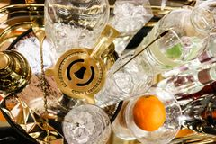 Cocktail hour - martini shaker on tray with various crystal glasses and bottles and an orange - top view and selective focus. Cocktail hour - A martini shaker on Royalty Free Stock Photo