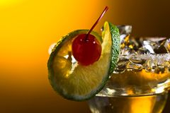 Cocktail with cherry and lime. Cocktail with ice , cherry and lime on yellow background Stock Photos