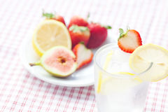 Cocktail with ice,lemon, fig and strawberries Royalty Free Stock Photo