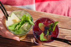 Cocktail with ice and lemon slice on wooden table Stock Image