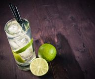Cocktail with ice and lime slice and space for text on old wood table Royalty Free Stock Photography
