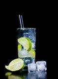 Cocktail with ice and lime slice with straw and space for text Royalty Free Stock Photos