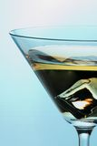 Cocktail with ice in Martini glass. Martini glass full of cocktail with one cube of ice on the bottom over aqua paper background Stock Photo