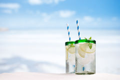 Cocktail with ice, rum, lemon and mint   in a  glass  on beach Stock Photo
