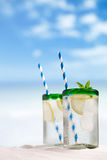 Cocktail with ice, rum, lemon and mint in a glass on beach stock photos