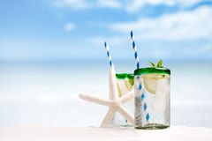 Cocktail with ice, rum, lemon and mint   in a  glass  on beach Stock Image