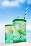 Cocktail with ice, rum, lemon and mint in a glass on beach royalty free stock images