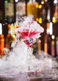Cocktail with ice vapor and splashing liquid stock photography
