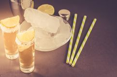 Cocktail ingredients and Tequila shots/cocktail ingredients and Tequila shots on a dark background. Toned. Bar tools beverage shaker straws lime cocktails ice royalty free stock photos
